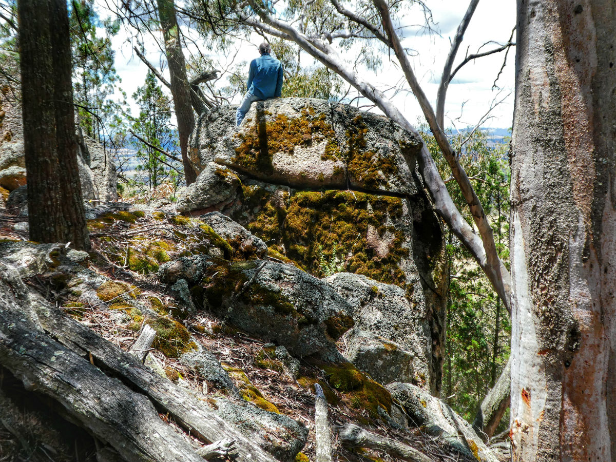 Ian Lunt in contemplation on top of a large granite rock