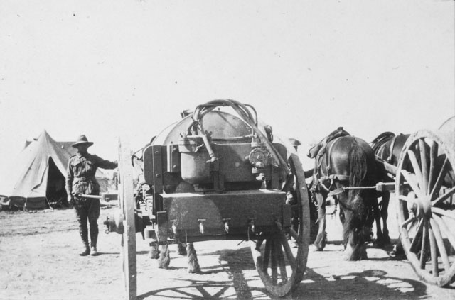 A horse-drawn water cart (tank) mark II (commonly known as a Furphy, after the Australian version manufactured in Ballarat) at a 1st AIF encampment. A second cart pulled by two draught horses is partly visible at right. Egypt, 1915.